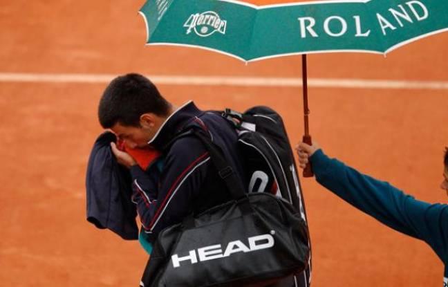 Novak quitte le court de la finale de Roland-Garros sous la pluie, le 10 juin 2012.