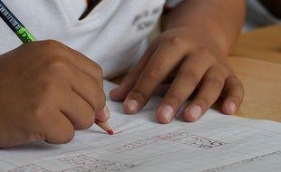 Un enfant faisant un test de mathématiques.