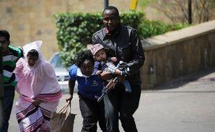 Un policier escorte des personnes qui quittent un centre commercial de Nairobi, dans lequel se déroule une prise d'otages, le 21 septembre 2013