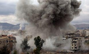 De la fumée s'échappe de bâtiments pilonnés par l'armée syrienne, à Kafr Batna, dans l'enclave rebelle de la Ghouta, près de Damas, le 22 février 2018.