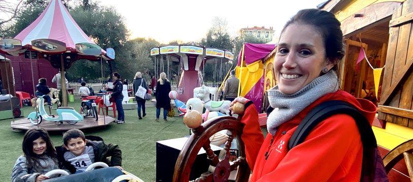 Marta Campana est à la barre d'un bateau du parc d'attractions à propulsion parentale, à Nice, pour amuser son fils Pau, 5 ans, et sa nièce Zoé, 7 ans