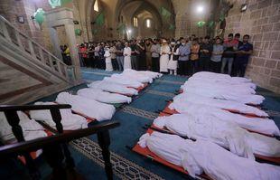 Des personnes en deuil prient à côté de victimes tués lors de frappes aériennes israéliennes durant la nuit dans la ville de Gaza le 16 mai 2021.