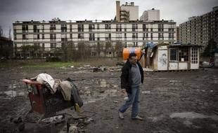 Un homme porte une bouteille de gaz dans un camp de roms à Ivry-sur-Seine, le 18 décembre 2014