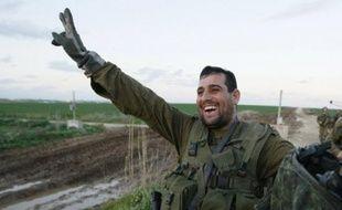 """Des photographes de l'AFP ont vu plusieurs groupes de soldats quitter le territoire palestinienn faisant le """"V"""" de la victoire, chargé de leur barda, parfois surmonté de drapeaux israéliens."""