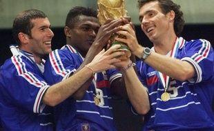 Zinédine Zidane, Marcel Desailly et Laurent Blanc en train d'admirer la coupe du monde en 1998.
