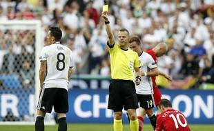 Referee Bjorn Kuipers shows a yellow card to Germany's Mesut Ozil, left, during the Euro 2016 Group C soccer match between Germany and Poland at the Stade de France in Saint-Denis, north of Paris, France, Thursday, June 16, 2016. (AP Photo/Christophe Ena)/HAS193/569429350904/1606162153