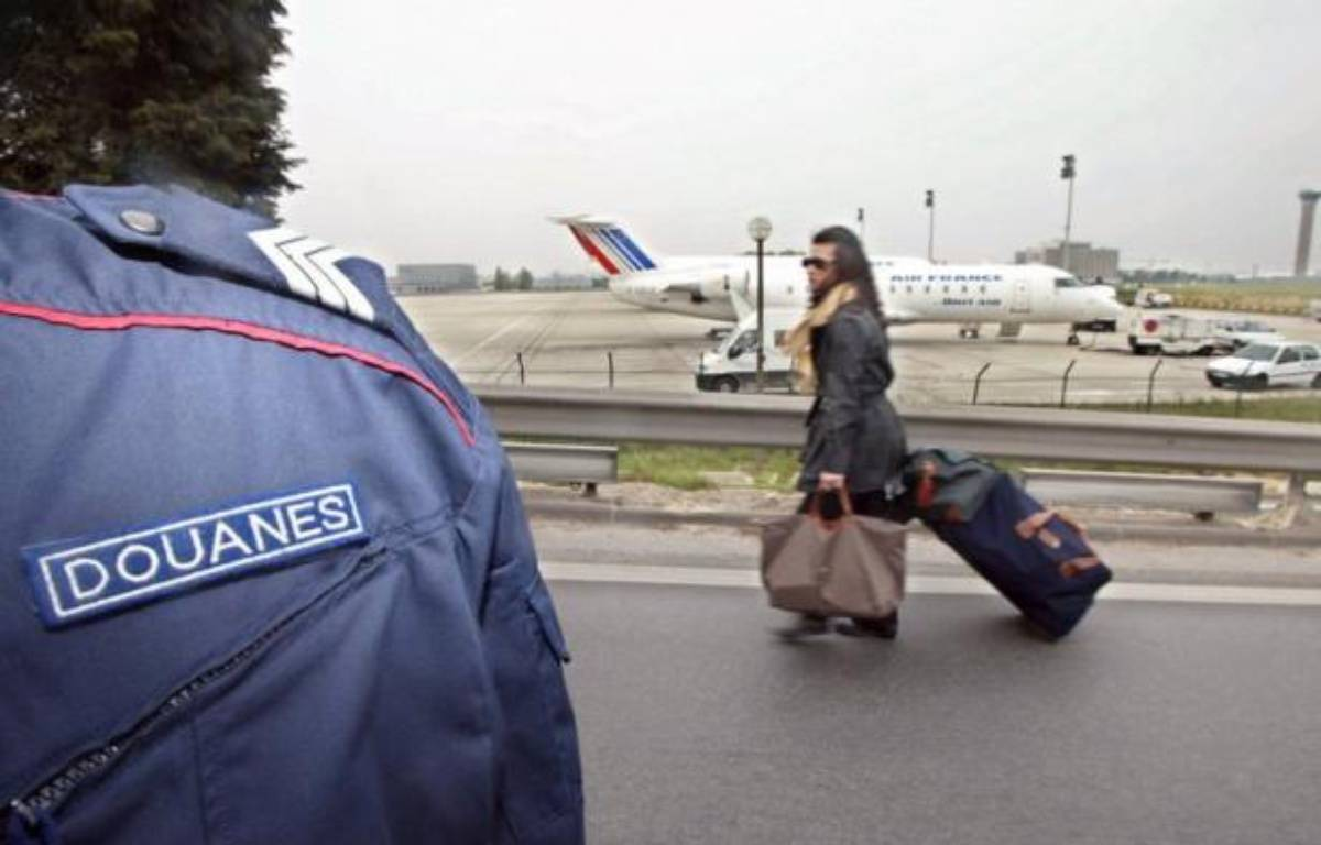 Sept douaniers de l'aéroport de Roissy soupçonnés d'avoir volé de l'argent liquide dans les valises de trafiquants de drogue présumés, ont été mis en examen pour vol en bande organisée, blanchiment et association de malfaiteurs, a annoncé samedi le parquet de Bobigny. A traveller pull her luggage in front of one of the French customs officer blocking an access road to a Roissy Charles-de-Gaulle airport terminal, 11 April 2002. Around 100 of the officers sat across the road leading to one of the airport terminals, in an ongoing campaign to win extra money. – Damien Meyer afp.com