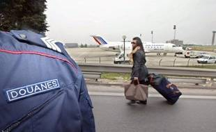 Sept douaniers de l'aéroport de Roissy soupçonnés d'avoir volé de l'argent liquide dans les valises de trafiquants de drogue présumés, ont été mis en examen pour vol en bande organisée, blanchiment et association de malfaiteurs, a annoncé samedi le parquet de Bobigny. A traveller pull her luggage in front of one of the French customs officer blocking an access road to a Roissy Charles-de-Gaulle airport terminal, 11 April 2002. Around 100 of the officers sat across the road leading to one of the airport terminals, in an ongoing campaign to win extra money.