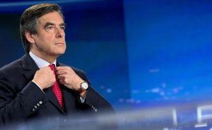 L'ancien Premier ministre François Fillon ajuste sa veste le 9 novembre 2014 sur le plateau parisien de TF1, avant son intervention télévisée