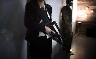 Une femme tient un Famas, le célèbre fusil d'assaut français