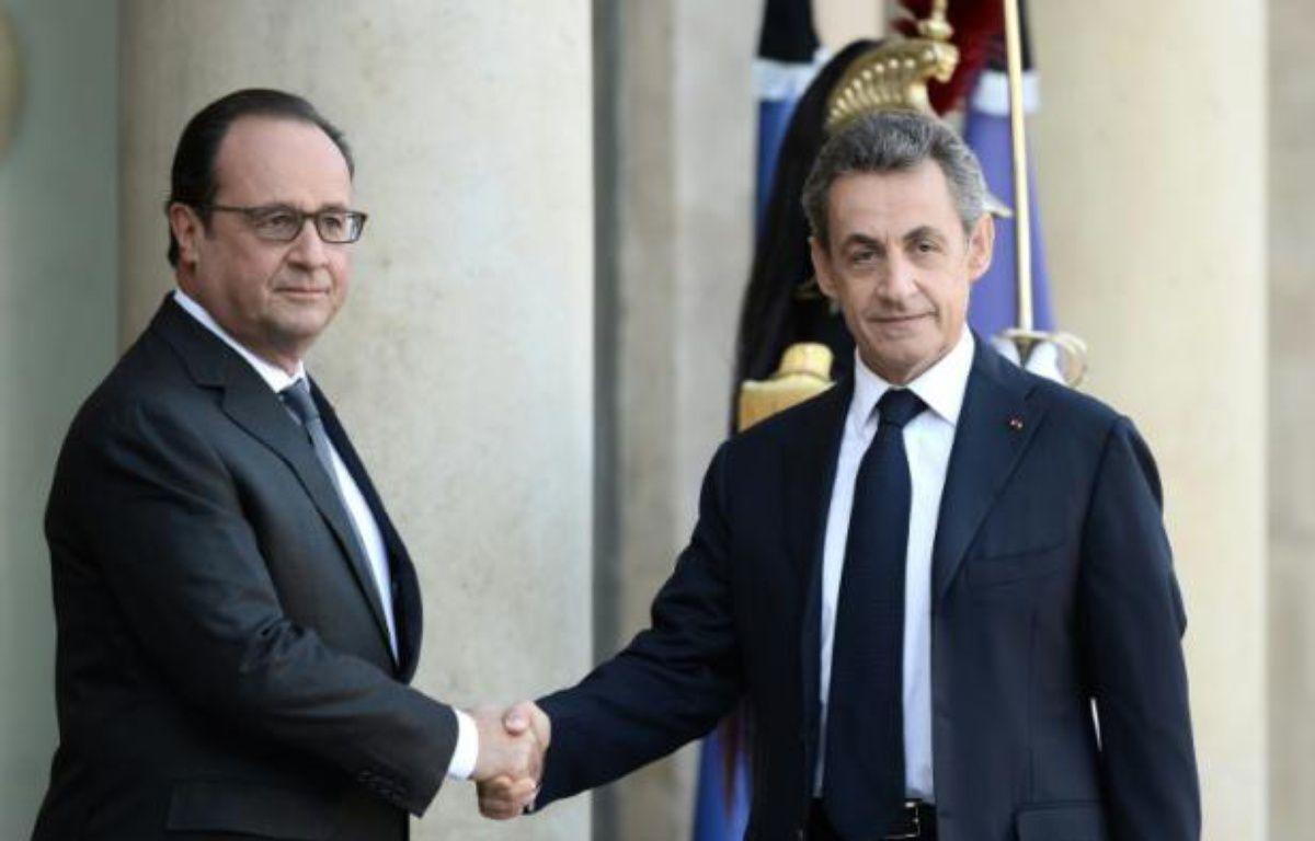 Le président français François Hollande (g) salue son prédécesseur à l'Elysée Nicolas Sarkozy à Paris le 15 novembre 2015 – STEPHANE DE SAKUTIN AFP