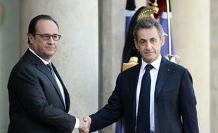 Le président français François Hollande (g) salue son prédécesseur à l'Elysée Nicolas Sarkozy à Paris le 15 novembre 2015