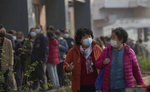 Des femmes passent devant des habitants faisant la queue pour recevoir des injections de rappel contre le COVID-19 sur un site de vaccination à Pékin, le lundi 25 octobre 2021.