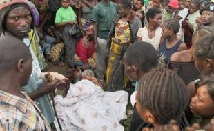 Des personnes se tiennent près d'une fosse après le massacre de 22 personnes par des rebelles ougandais, le 20 octobre 2014 à Beni, dans l'est de la RDC