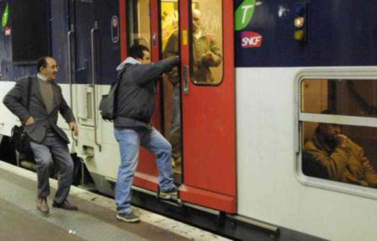 Un homme tente de monter à bord d'un RER à Paris. – REUTERS/Gonzalo Fuentes