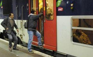 Un homme tente de monter à bord d'un RER à Paris.