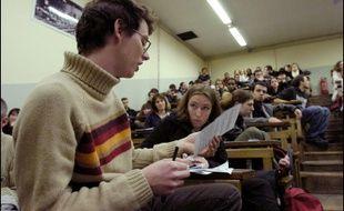 Des étudiants participent à une assemblée générale dans l'amphithéatre d'une université.