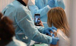 Une femme en train de se filmer pendant la vaccination.