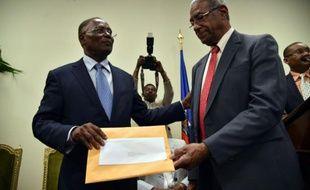 François Benoit (d), le président de la commission électorale indépendante présente son rapport recommandant l'annulation du premier tour de le présidentielle en présence du président provisoire Jocelerme Privert (g) à Port-au-Prince, le 30 mai 2016