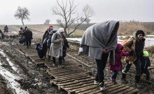 Des migrants traversent un champ boueux après avoir passé la frontière serbo-macédonienne près du village serbe de Miratovac, le 27 janvier 2016