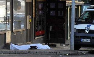 Un corps recouvert d'un drap repose dans une rue d'Hyvinkaa, en Finlande, après une fusillade, le 26 mai 2012.