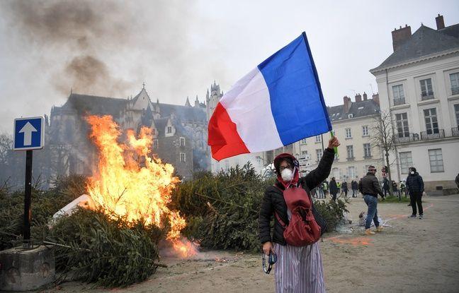 Un manifestant devant un tas de sapin incendié en marge d'un défilé de «gilets jaunes» à Nantes.