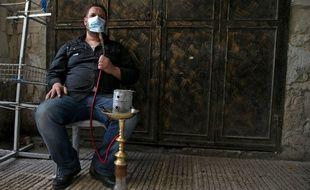 Un homme qui fume la chicha sous son masque