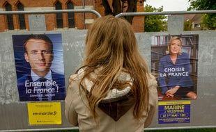 Une citoyenne devant les affiches de campagnes de Marine Le Pen et d'Emmanuel Macron . Le 29/04/ 2017.AFP PHOTO/PHILIPPE HUGUEN