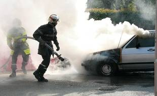Pompiers en intervention.    Feu, voiture en feu sur le voie publique. Flammes.  Voiture brulee.