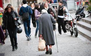 Une personne âgée dans une rue piétonne, avec un cabas et une béquille. Illustration sur la vieillesse.