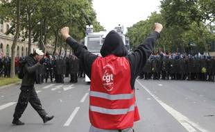 Un manifestant portant un gilet de la CGT face des à agents des forces de l'ordre lors du défilé contre la loi travail le 14 juin 2016 à Paris.