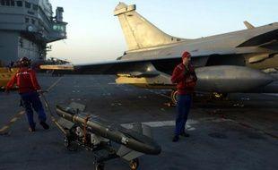 Des techniciens s'affairent autour d'un avion Rafale revenant d'une mission en Irak, sur le pont du porte-avions Charles de Gaulle, le 26 février 2015