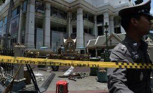 Un policier thaïlandais patrouille près du cordon de sécurité entourant le site d'un attentat contre un temple hindouiste, dans un quartier touristique et commercial de Bangkok, le 18 août 2015