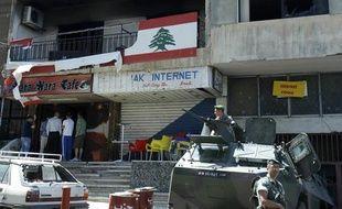 Des soldats de l'armée libanaise dans leur blindé montent la garde devant les bureaux incendiés du Mouvement Arabe après une nuit d'affrontements à Beyrouth (lundi 21 mai 2012)