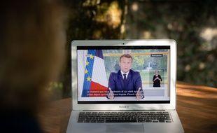 Une femme regarde l'allocution du président Macron, dimanche 14 juin.