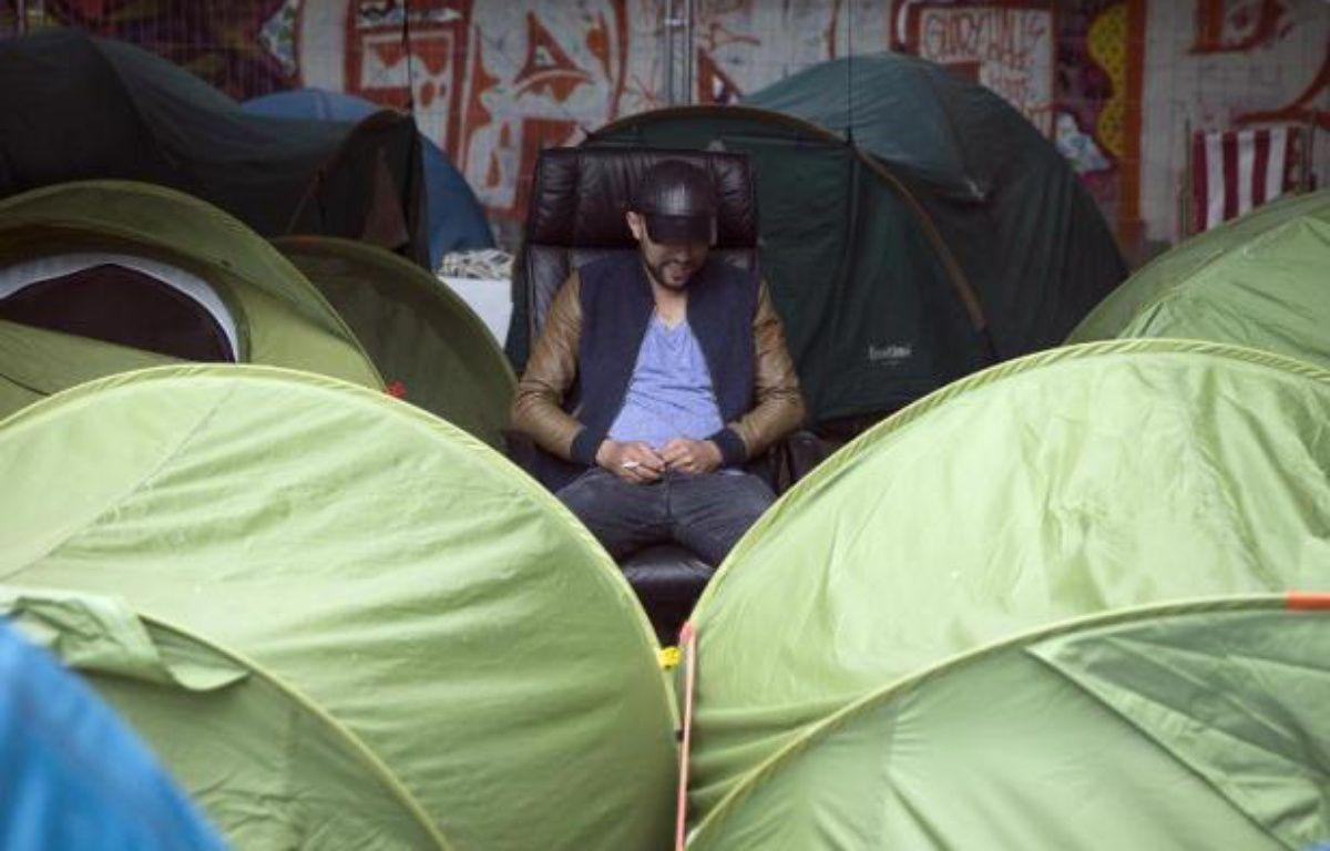Un migrant installé au milieu d'un campement de tentes, près de la gare d'Austerlitz, à Paris, le 14 juin 2015 (Archives) – JOEL SAGET AFP