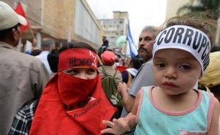 Un enfant porte un bandeau dénonçant la corruption, lors d'une manifestation à Tegucigalpa le 3 juin 2015 pour réclamer la démission du président hondurien Juan Orlando Hernandez