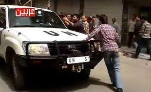Capture d'écran d'une vidéo montrant un véhicule des observateurs de l'ONUs'enfuir après des coups de feu tirés sur des manifestants.