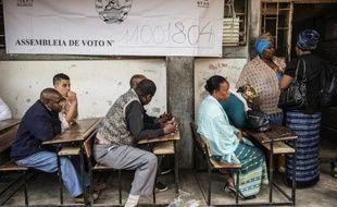 Des électeurs mozambicains, assis à des pupitres dans une école de Maputo, attendent leur tour pour voter, le 15 octobre 2014