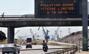 Des automobilistes circulentsous un panneau de limitation de la  vitesse, réduite à 70km/h en raison de la canicule qui augmente les  risques de pollution à l'ozone, sur  l'autoroute du Littoral à Marseille, le 18 août 2009.