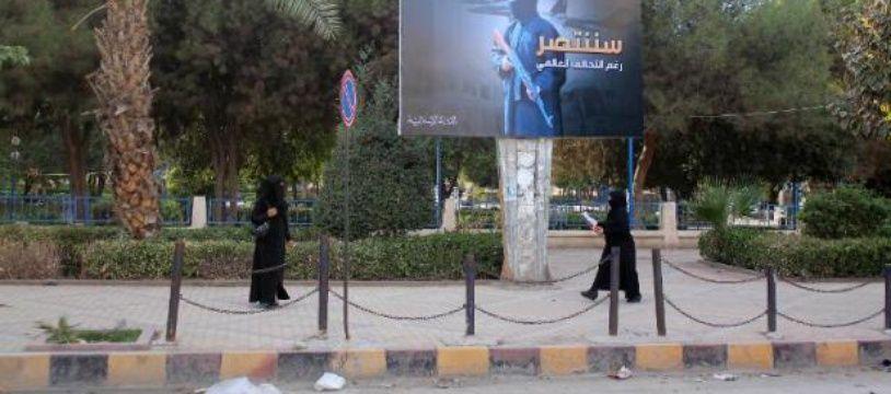 """Des femmes entièrement voilées marchent devant un panneau du groupe jihadiste EI proclamant """"Nous serons victorieux"""", le 1er novembre 2014 dans la ville de Raqa, en Syrie"""