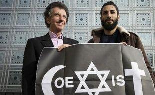 Le street-artiste Combo (D) et le président de l'Institut du monde arabe Jack Lang posent le 8 février devant l'Institut du monde arabe à Paris