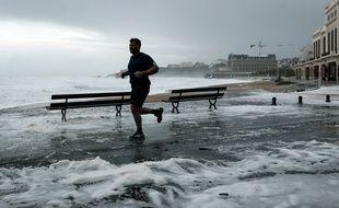 Un homme court au bord de la mer sur la Grande Plage de Biarritz, dans le sud-ouest de la France, le 3 novembre 2019, lors de la tempête Amélie.