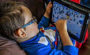 Un enfant joue sur une tablette.
