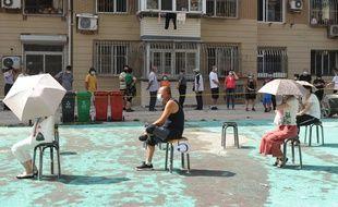 Des gens attendent assis, suffisamment éloignés les uns des autres, avant d'être testé au Covid-19 dans un centre de fortune à Dalian, dans la province du Liaoning au nord-est de la Chine, le 28 juillet 2020.