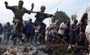 Des manifestants burundais opposés à un troisième mandat du président Pierre Nkurunziza sautent par dessus les cendres d'une barricade, le 1er mai 2015 à Bujumbura