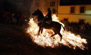L'un après l'autre, les chevaux et leurs cavaliers s'élancent par-dessus les bûchers qui jalonnent les rues étroites de San Bartolome de Pinares, un village du centre de l'Espagne, dans un ballet avec le feu qui se répète depuis des centaines d'années.