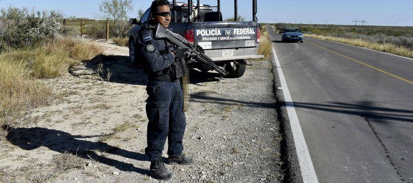 Un policier garde l'entrée de Villa Union, au Mexique, après de violents affrontements entre narcotrafiquants et forces de l'ordre le 1er décembre 2019.