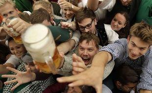 Des jeunes trinquent à la bière lors de l'ouverture du 184e Oktoberfest à Munich en Allemagne, samedi 16 septembre 2017.