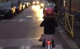 Capture d'écran de la vidéo montrant une enfant à vélo slalomant entre les voitures.